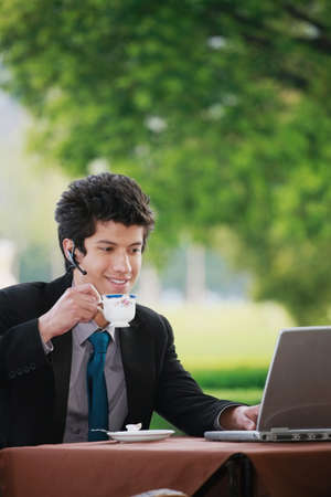 Businessman having tea while using laptop photo