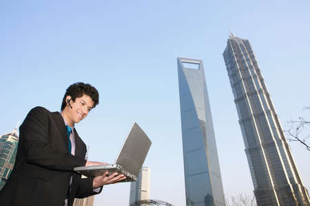 Businessman using laptop outdoors photo