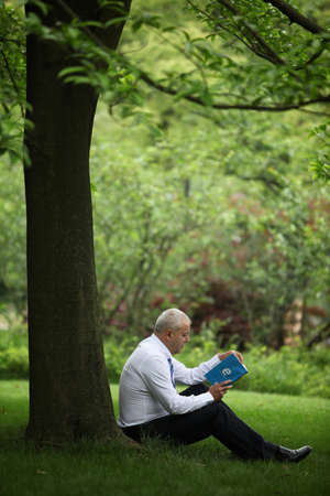 Businessman reading book under a tree photo