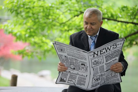 Businessman reading newspaper photo