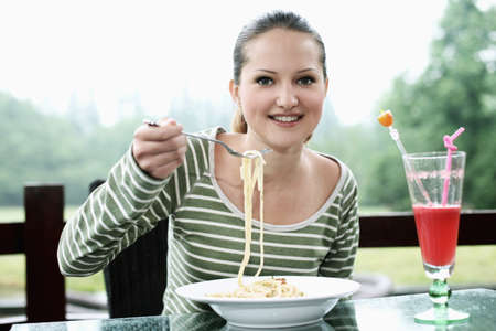 Woman enjoying a plate of pasta Stock Photo - 24303321