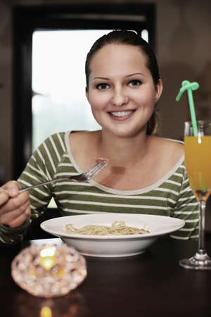 Woman enjoying a plate of pasta photo