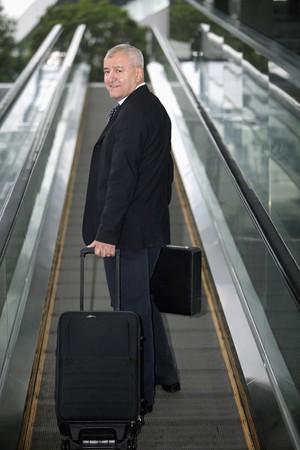 southern european descent: Businessman on escalator, pulling suitcase