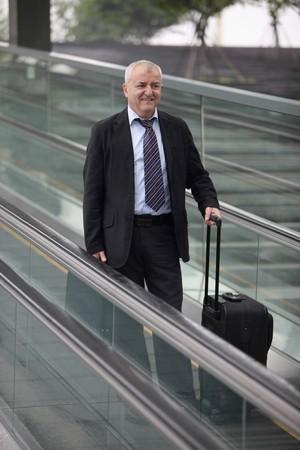 Businessman on escalator, holding suitcase photo