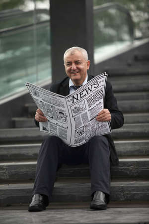 Businessman sitting on the stairs reading newspaper photo