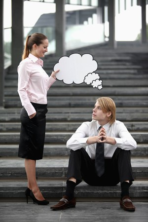 Businesswoman holding thinking bubble above businessmans head photo