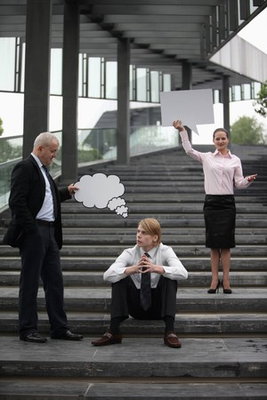 Businessman holding thinking bubble above another businessmans head, businesswoman holding speech bubble photo