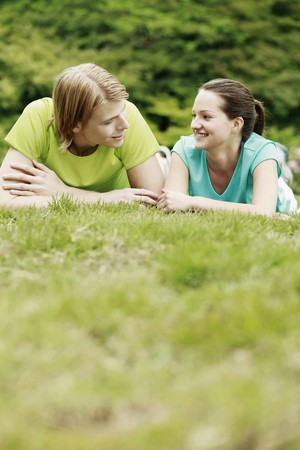 Man and woman resting on the grass photo