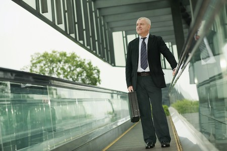 Businessman on escalator, carrying briefcase photo