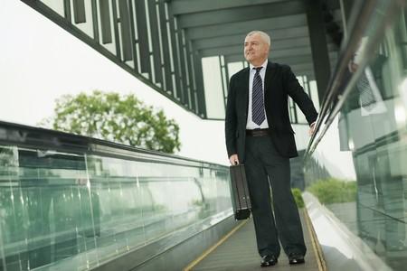 Businessman on escalator, carrying briefcase photo