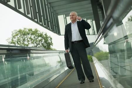 Businessman on escalator, talking on the phone photo