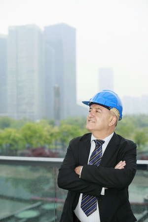 Businessman with hardhat crossing his arms photo