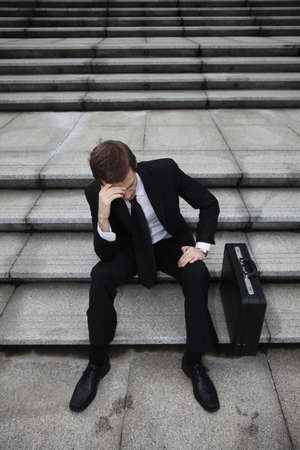 Businessman sitting on stairs looking depressed photo