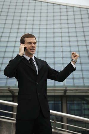 Businessman talking on mobile phone and shaking his fist photo