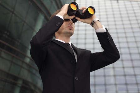 Businessman looking through binoculars photo