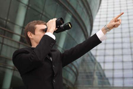 central european ethnicity: Hombre de negocios mirando a trav�s de binoculares y se�alando hacia delante Foto de archivo