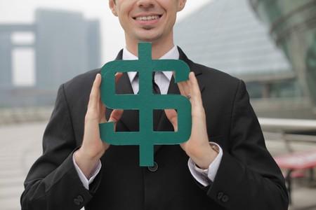 Businessman holding dollar sign photo