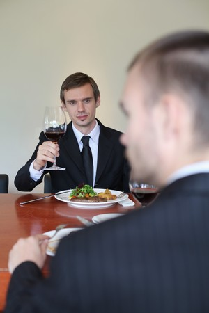 Businessman raising a glass of wine photo