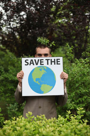 Businessman holding a card saying Save the Planet photo