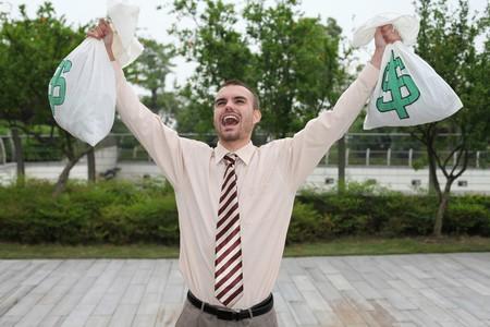 Businessman holding money bags photo