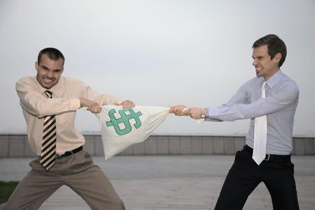 pulling money: Businessmen pulling at money bag
