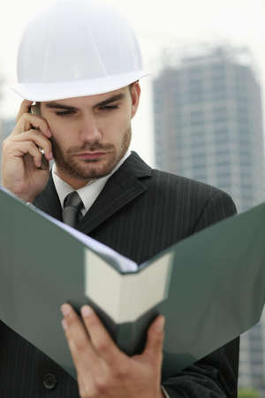 Businessman with hard hat talking on the phone and reading document in file photo