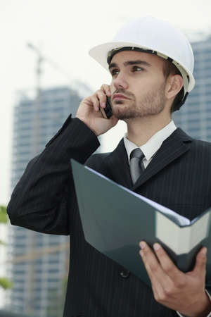 Businessman with hard hat talking on the phone and holding a file photo