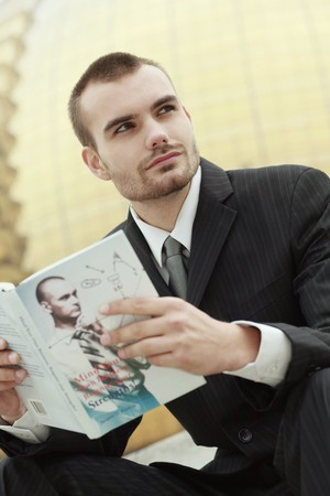 Businessman reading a book outdoors photo
