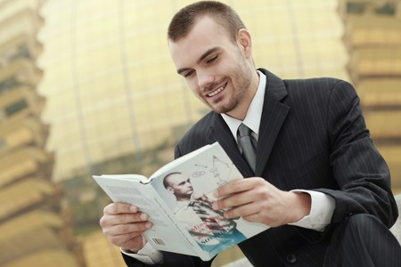 man holding book: Businessman reading a book outdoors