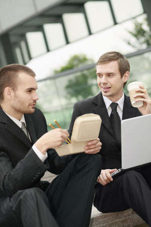 Businessmen eating while working outdoors photo