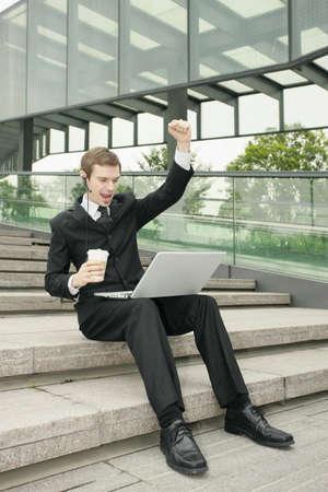 Businessman using laptop with fist raised photo
