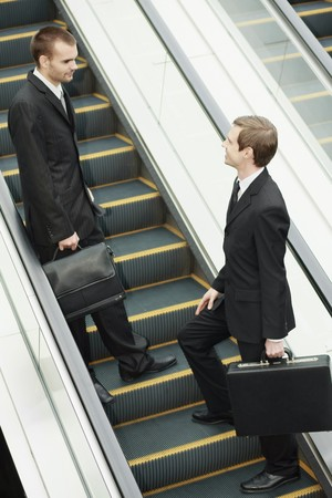 central european ethnicity: Empresarios hablando sobre la escalera mec�nica  Foto de archivo