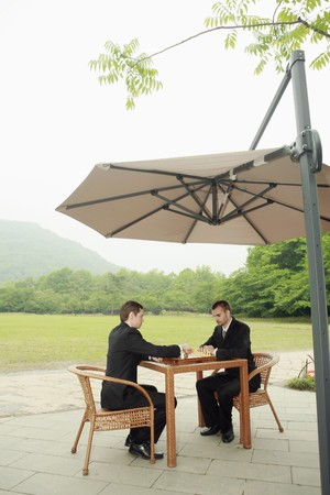 Businessmen playing chess outdoors photo