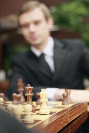 Businessmen playing chess outdoors, focus on chess piece photo