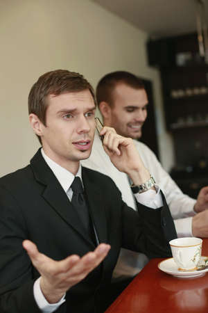 Businessman talking on the phone while his colleague smiling in the background photo