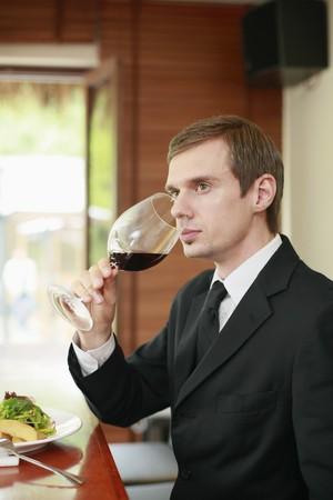 Businessman drinking wine Stock Photo