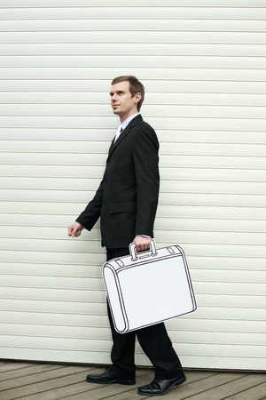 Businessman holding briefcase, walking away photo