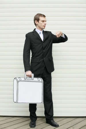 Businessman holding briefcase looking at time photo
