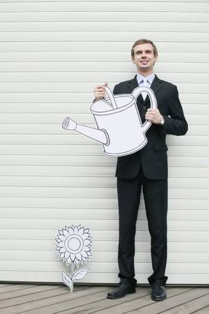 Businessman holding watering can photo