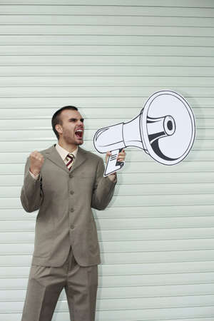 Businessman shouting through megaphone photo