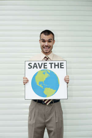 Businessman holding a card saying 'Save the Planet' photo
