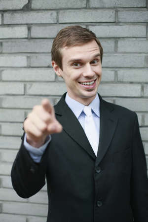 Businessman smiling and pointing finger photo
