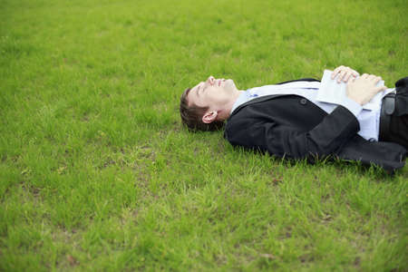 Businessman lying on the grass with book on his body photo