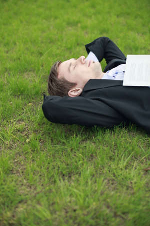 Businessman lying on the grass with book on his chest photo