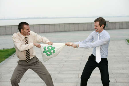 Businessmen pulling at money bag photo