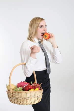 Businesswoman biting tomato while carrying a basket of vegetable and fruits photo