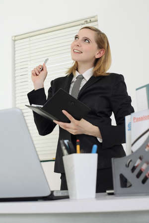 Businesswoman writing in organizer photo