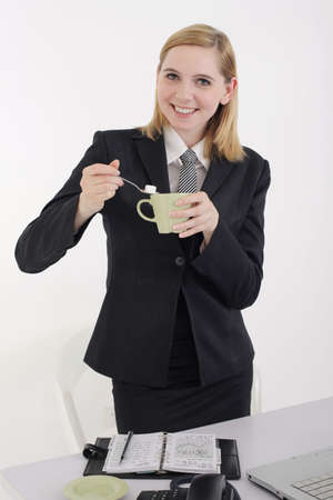 Businesswoman making a cup of coffee photo