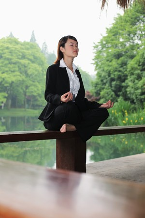 Businesswoman meditating on bench photo