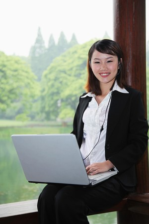 Businesswoman using laptop, smiling Stock Photo - 7839286